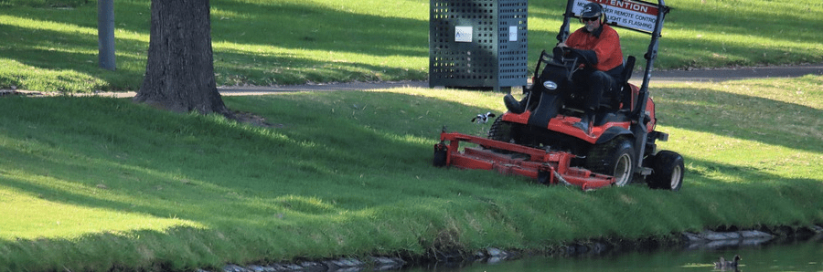 A commercial zero turn mower cutting grass at a park.
